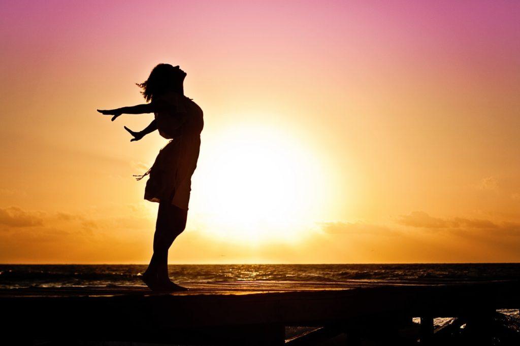 silhouette di donna che respira a braccia aperte al tramonto in riva al mare